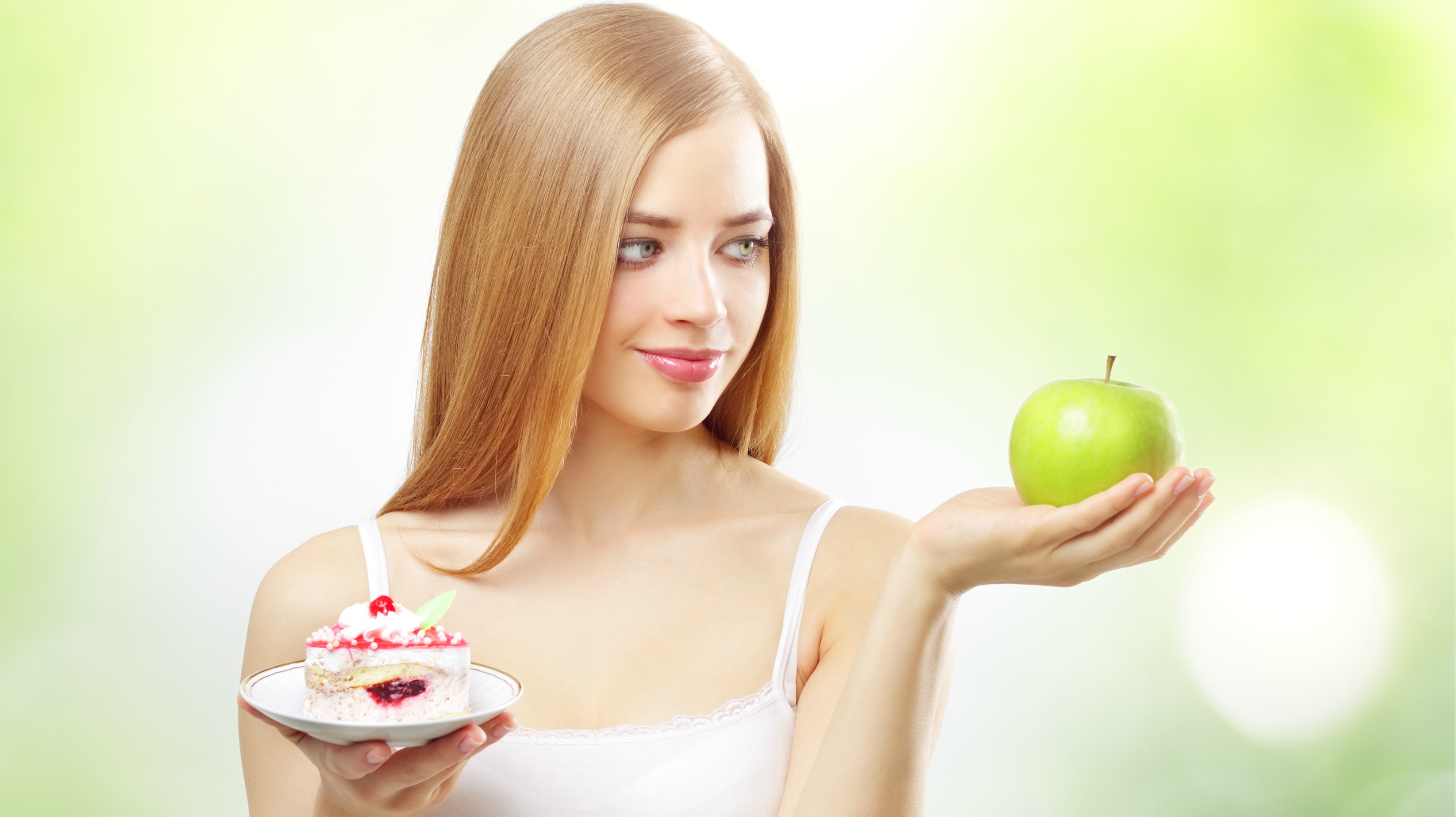 girl holding a cake and apple on a light background